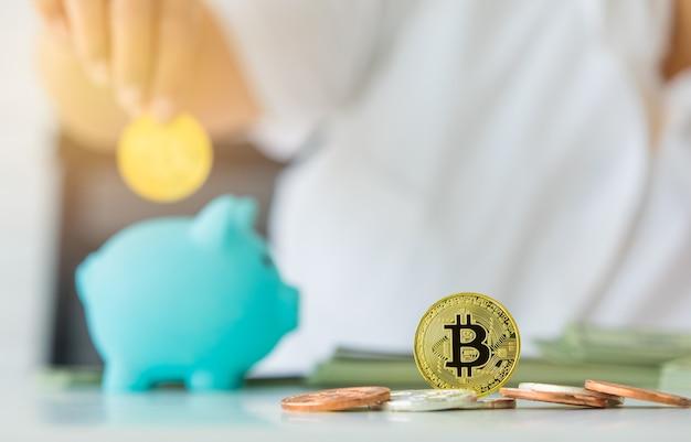 ビットコインのお金のシンボルを持っている手であるコインに選択的に焦点を合わせ、それを貯金箱に入れます。将来のための暗号通貨の宝と投資の概念。