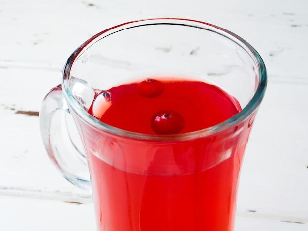 ガラスのコップの中の新鮮な飲み物に浮かぶクランベリーに選択的な焦点