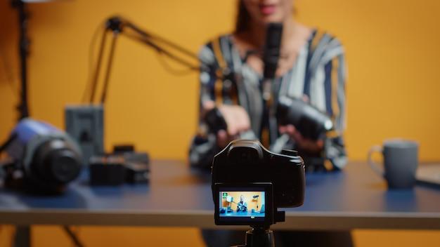 카메라 렌즈에 대해 이야기하는 전문가에 대한 선택적 초점. 온라인 인터넷 웹 쇼를 위한 비디오 사진 장비를 말하는 소셜 미디어의 콘텐츠 제작자 뉴 미디어 스타 인플루언서
