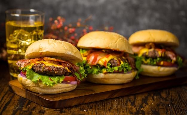 ビーフバーガー、揚げタマネギ、ほうれん草、ケチャップ、チーズを使ったハンバーガーを厳選。木の板のロフトの背景にビールを添えて。