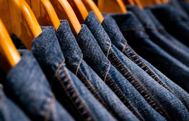 옷이 게에서 선반에 매달려 재킷 청바지에 선택적 초점.