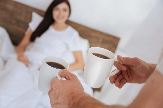 彼のガールフレンドのための朝食を彼らのベッドに持って来ている間、コーヒーでいっぱいの2つのカップを持っている男性の手に選択的な焦点