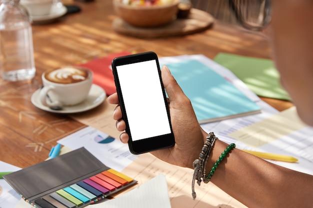 空白の白いモックアップ画面を備えた最新の携帯電話に選択的に焦点を当てる