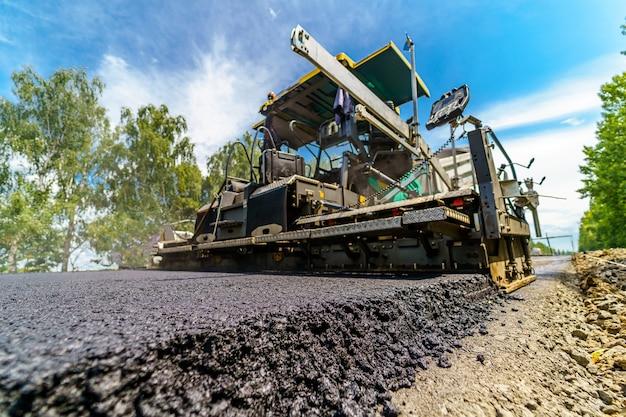 新しく敷設されたアスファルトに選択的に焦点を当てます。道路でアスファルトをお世辞するための重い特別な技術。建設現場。