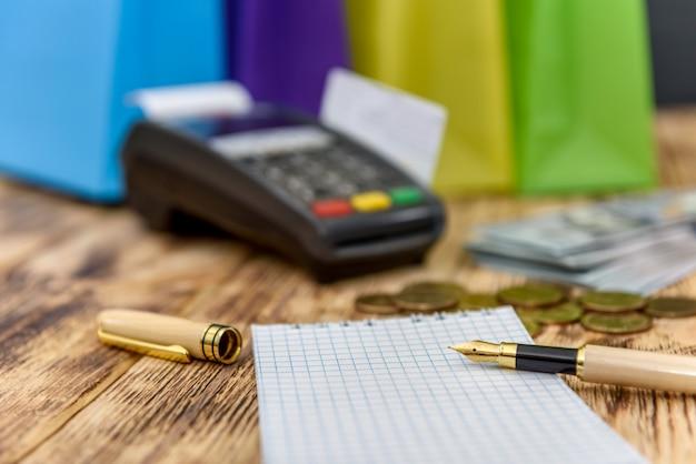 Селективный фокус на блокноте с ручкой против банковского терминала