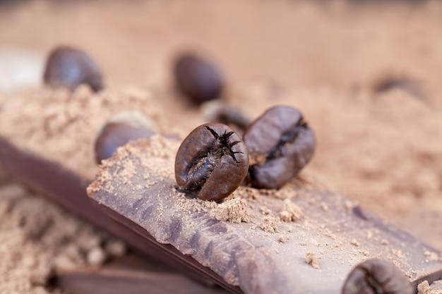 大量のチョコレートと一緒にコーヒー豆の1つ、シュガーチョコレート、ローストコーヒー豆に選択的に焦点を当てる