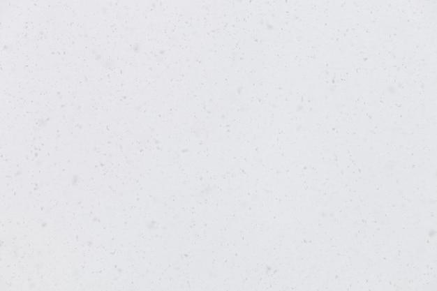 吹雪の背景に空から降る本物の雪に選択的に焦点を当てる
