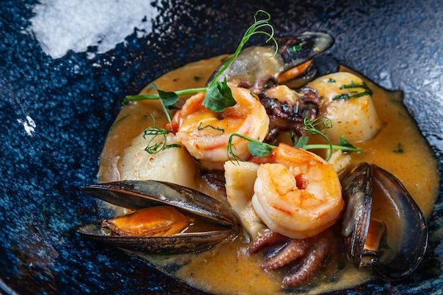 Селективный акцент на вкусные тушеные морепродукты в сливочном соусе. креветки, морские гребешки, мидии, осьминог в темной тарелке. закройте копировать пространство здоровая пища