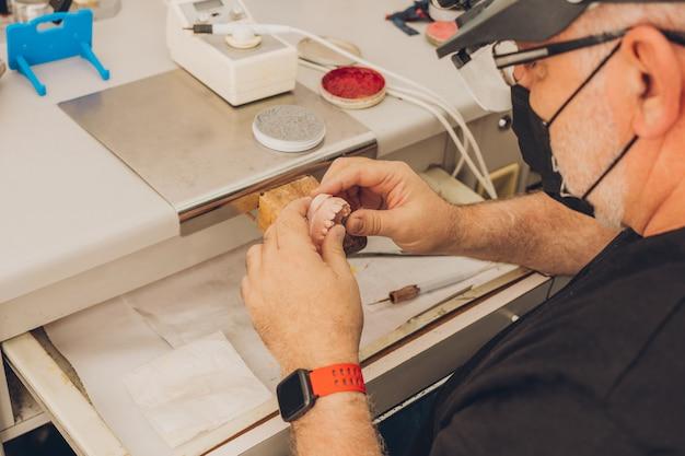 ポーセレンクラウンを作成するために歯科技工所の歯科技工所で歯科用金型を使用して作業するワークショップテーブルに座っている白人の成人男性の手に選択的に焦点を当てます。