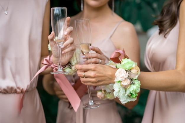 自然の花とシャンパングラスで飾られたピンクのシルクのドレスを着た花嫁介添人の手に選択的に焦点を当てる
