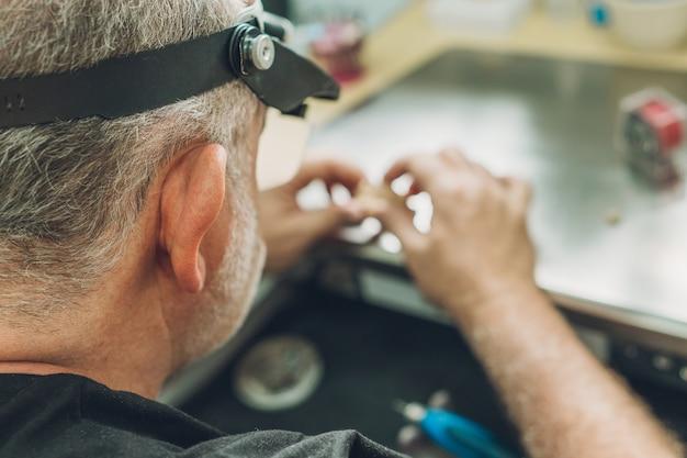 ポーセレンクラウンの歯科技工所で働く白人男性の頭に選択的に焦点を当てる
