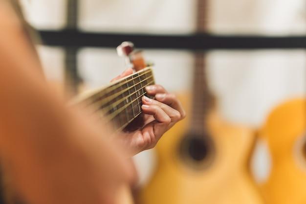女性が演奏しながらクラシックギターの弦に選択的に焦点を当てる