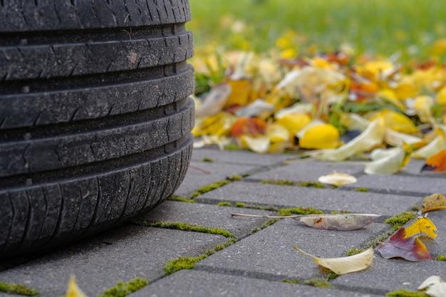 秋の日に舗装に横たわっている車のタイヤのトレッドに選択的に焦点を当てる