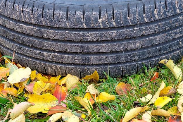 秋の日に草の上に横たわっている車のタイヤのトレッドに選択的に焦点を当てる