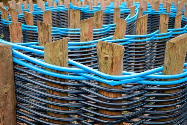 黒と青のプラスチックパイプが絡み合って作られた木製の柵柱に選択的に焦点を当てます。ランドスケープデザインにおけるポリプロピレン配管パイプの代替使用。抽象的な背景。