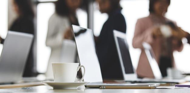 Селективный акцент на рабочий стол, группа неузнаваемых деловых женщин, стоящих вместе в офисе во время перерыва. работа в команде сотрудников женского пола, принимая с расслабиться в размытие фона.