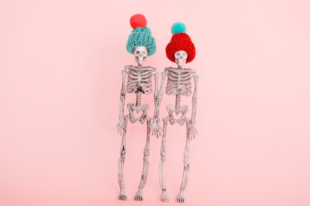 Selective focus pair of skeletons wearing cute knitted hat on a pink background