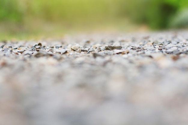 Selective focus on pebbles of gravel ground in natural sunlight background