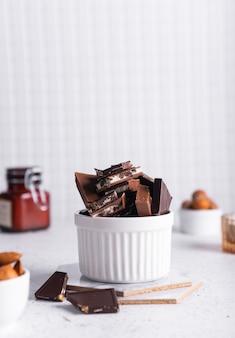 선택적 초점. 밝은 배경에 세라믹 흰색 컵에 우유와 쓴 초콜릿 조각