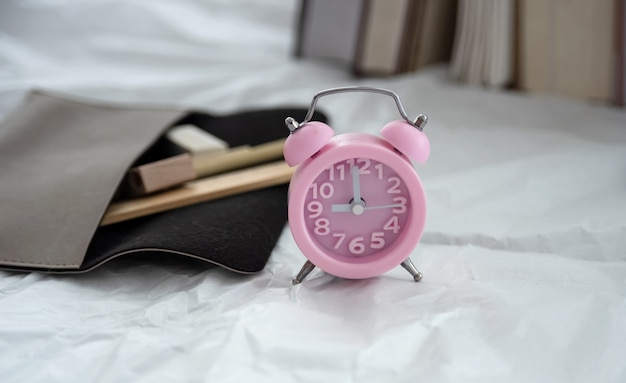 In selective focus of pink alarm clock put in front of blurred pencil case and books stacked