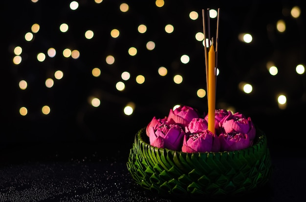 Selective focus on pink lotus flower decorates on banana leaves krathong with bokeh lights background for thailand full moon or loy krathong festival.
