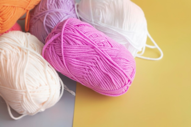 In selective focus of pink yarn ball put on yellow surface,blurry light around