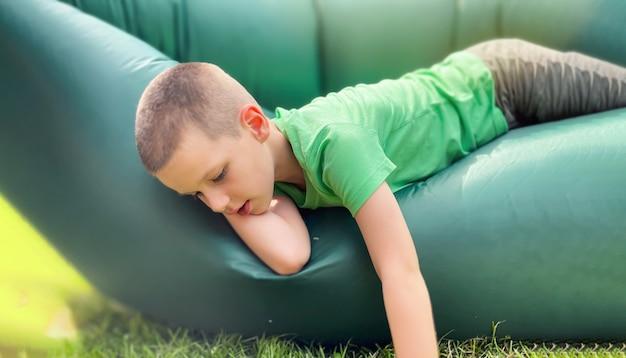 선택적 초점, 7세 백인 소년의 초상화, 녹색 티셔츠를 입은 람자크, 부풀릴 수 있는 안락 의자에 쉬고 있습니다. 편안한 야외 및 해변 레크리에이션, 여름 및 휴가 개념.
