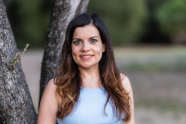 木に寄りかかって公園で笑顔の中年ラティーナの女性の選択的な焦点の肖像画