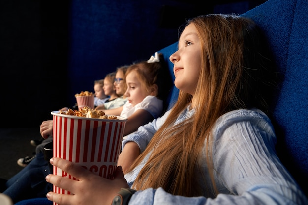 Selective focus of pretty little girl holding popcorn bucket, sitting with friends in comfortable chairs in cinema. children watching cartoon or movie, having fun
