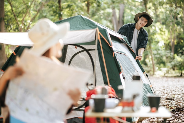 セレクティブフォーカス、キャンプテントの前の椅子に座って紙の地図で方向を確認しているきれいな女性、彼女の後ろにテントを張っているハンサムなボーイフレンド、彼らは休暇で森でキャンプするのを喜んでいます