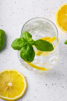 Selective focus, pure refreshing water with lemon and basil in a glass glass, on a light background