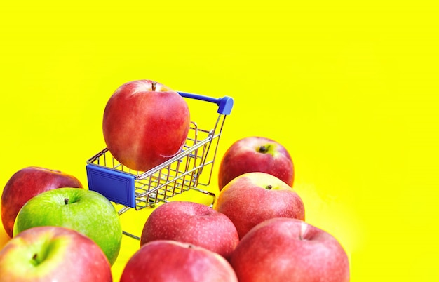 Selective focus on red apples on mini shopping cart with yellow background