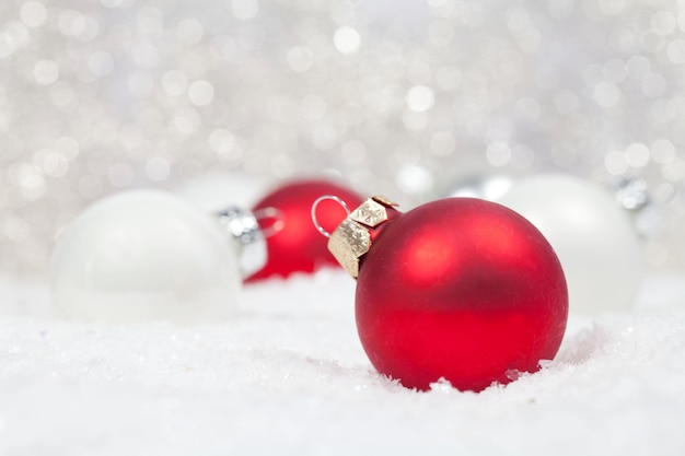 Selective focus of red and white christmas bulbs in the snow with bokeh lights on the background