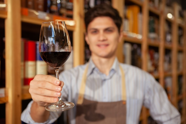 Selective focus on a red wine glass in the hand of cheerful sommelier. winemaker working at his shop