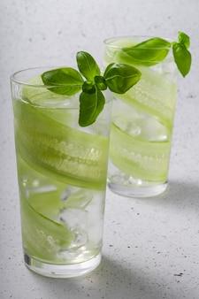 セレクティブフォーカス、スライスしたキュウリとさわやかなドリンク、緑のバジルの葉の背の高いグラスに