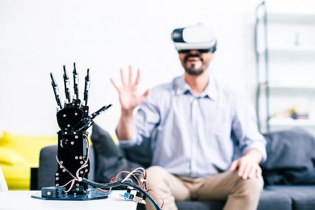 Selective focus of a robotic hand with a cheerful man sitting in the background and testing it