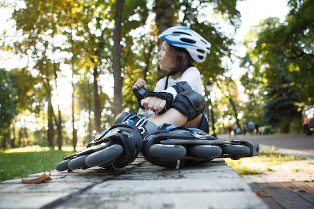 Selective focus on rollerskates young boy is wearing, resting in the park