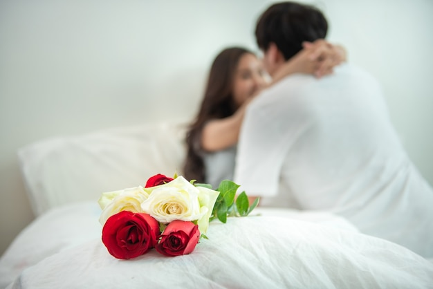 Selective focus on rose, asian young couple hug spend time together on bed,valentine day concept.hugging, kissing and enjoying man and woman while celebrating saint valentine.