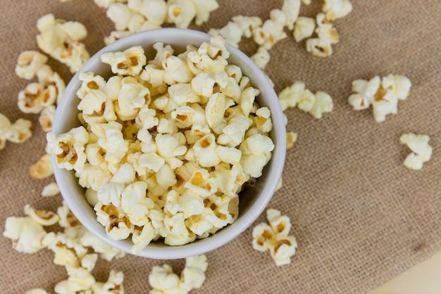 Селективный фокус соль попкорн или попкорн в белый шар на мешок с деревянными фоне. попкорн - это закуска или десерт. попкорн с copyspace.