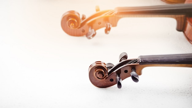 In selective focus of scroll and pegbox of violin, blurry light around