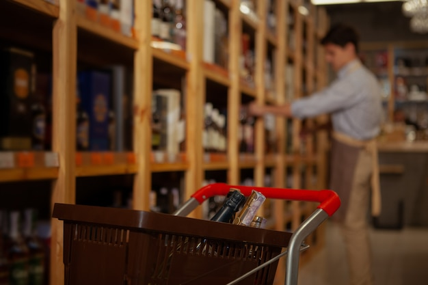 Selective focus on a shopping cart with bottles, wine shop owner organizing drinks on the shelves