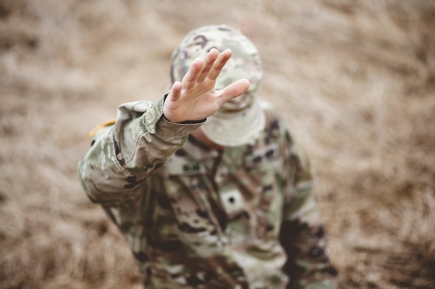 Selective focus shot of an american soldier with his hand raised above