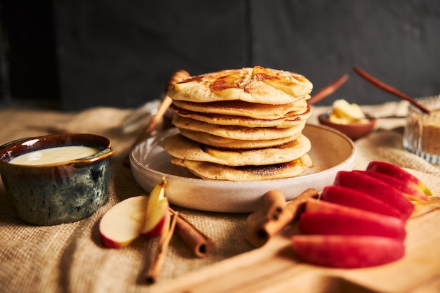 Selective focus shot of apple pancakes with apples and other ingredients on the table