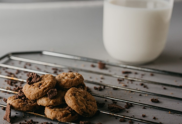 Colpo di messa a fuoco selettiva della griglia di cottura con deliziosi biscotti al cioccolato rotondi e una tazza di latte