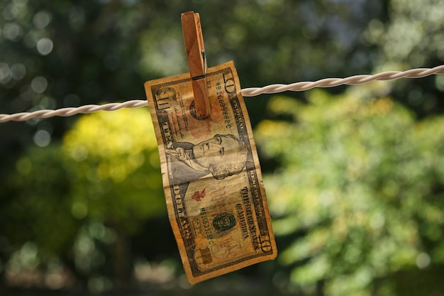 Selective focus shot of a banknote hung from a wire with a clothespin