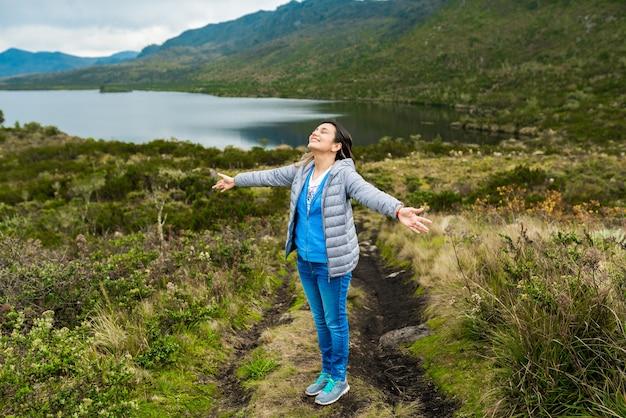 Messa a fuoco selettiva di una bellissima giovane donna che si gode la natura vicino a un lago