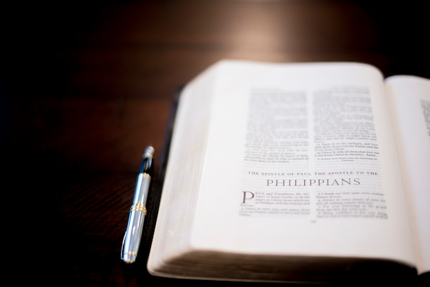 A selective focus shot of the bible with a pen on the side