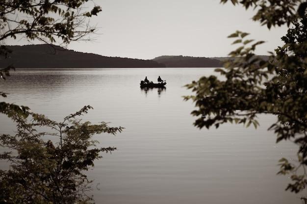 Colpo di messa a fuoco selettiva di una barca su un lago la sera