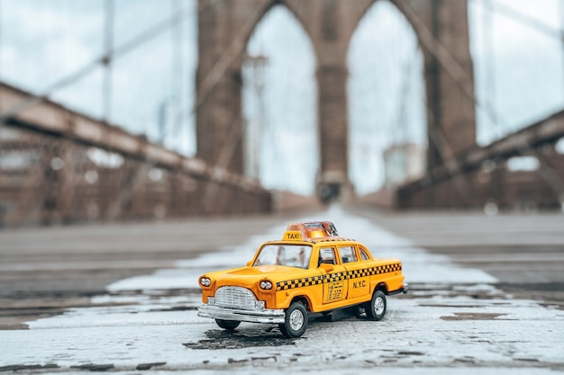 Selective focus shot of a classic yellow taxi model on an empty brooklyn bridge