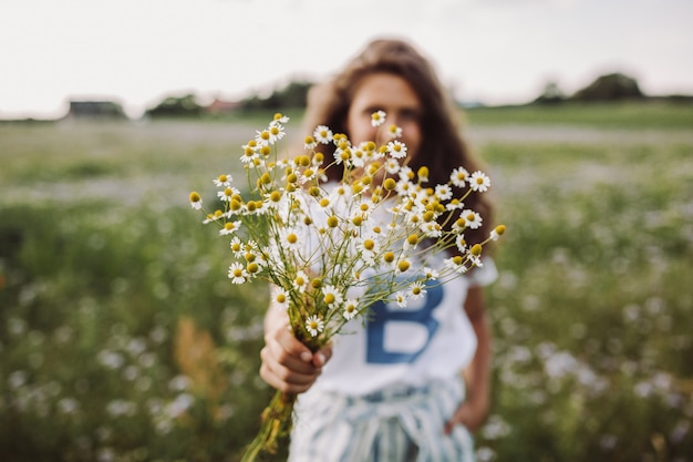 Selective focus shot of a curly model standing in a filed holding a bouquet of daisies